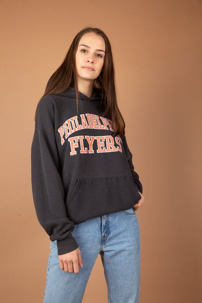 This ice-hockey jumper is faded black with orange and white print 'Philadelphia Flyers' across the front. This oversized hoodie is finished off with a kangaroo pouch style pocket and a hood.