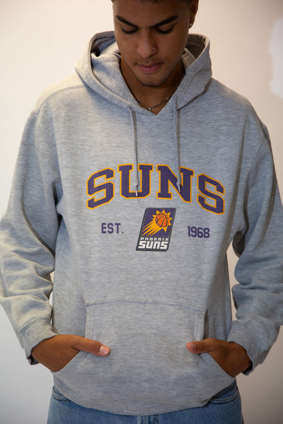 the model wears a grey hoodie with a phoenix suns logo on the front