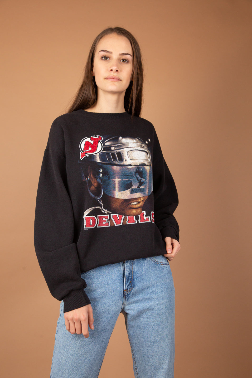 This NHL Devils Sweater is faded black in colour with a futuristic print of a man in a helmet, reflecting an ice hockey player. Branded Devils with the logo above, this is a hella cool sweater.