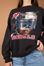 Load image into Gallery viewer, This NHL Devils Sweater is faded black in colour with a futuristic print of a man in a helmet, reflecting an ice hockey player. Branded Devils with the logo above, this is a hella cool sweater.