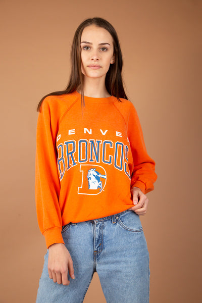 This must-have sweater is orange with a blue and white print of 'Denver Broncos' and the logo on the front. A stretched out neckline and ribbed sleeves, neckline and waistline make this a cosy, baggy fit.
