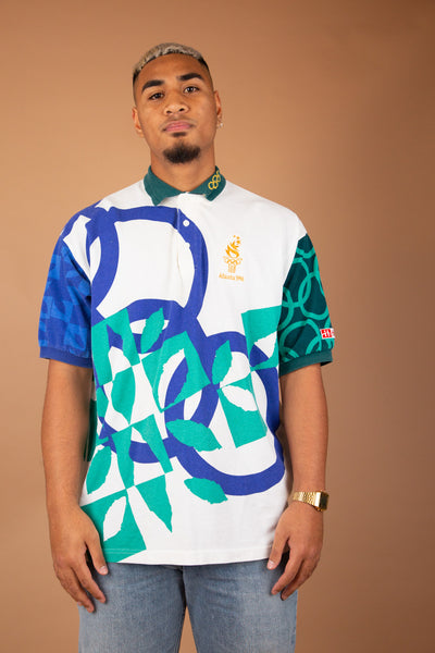 sick polo from the 1996 Atlanta olympics with teal and blue abstract patterns across it and gold olympic detailing