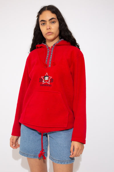 This must-have red sweater is a fleece-like material with a hood, quarter-zip, draw strings and a kangaroo-style pouch. Patterned along the neckline and zip with a Betty Boop appliqué on the front.
