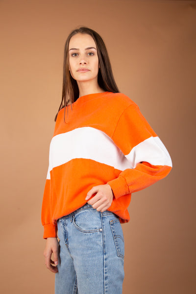 This must-have jumper is bright orange and has a white horizontal stripe across the chest and arms. Ribbed cuffs, neckline and waistline add to the baggy fit.