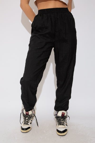 Model wearing black trackpants, magichollow