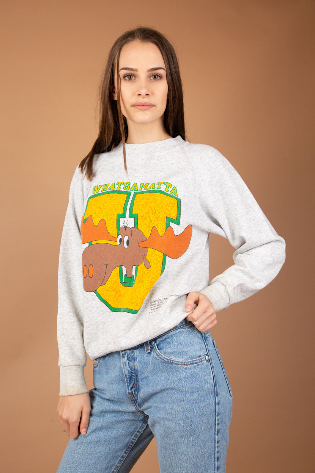 Grey in colour, this vintage sweater has a giant yellow and green 'U' print on the front with Bullwinkle J Moose from 'Rocky and his friends.' Whatsamatta printed above with small writing detail on bottom left of jumper.