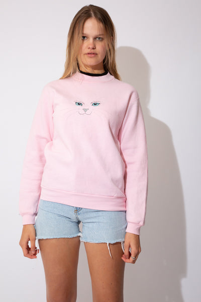Pink crew neck sweater with a black neckline under-layer and a cute kitty face on the front.