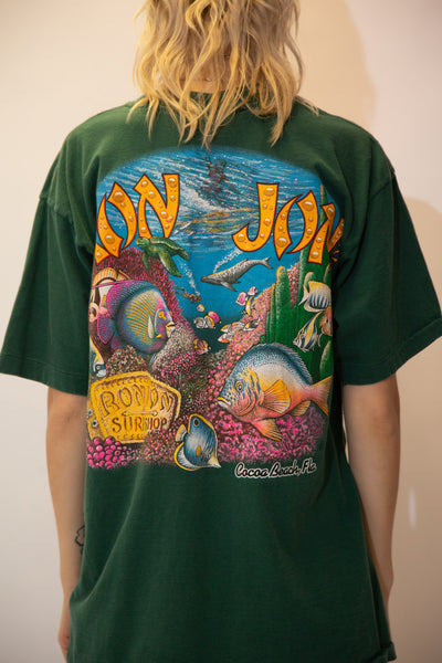 Dark green in colour with a large ocean print on both the front and back, this single-stitch tee is in a crew neck style and has a left chest pocket. Repping Ron Jon Surf Shop on both sides.