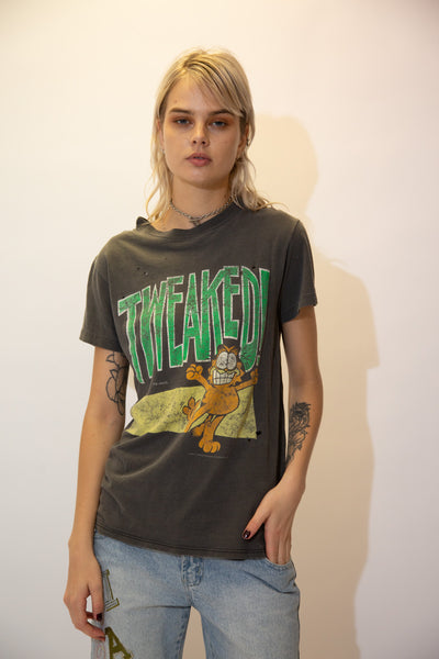 Dark grey in colour, this single stitch tee has a large green 'Tweaked' spell-out across the front with a buzzed looking Garfield printed below. Dated 1978