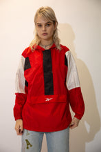 Load image into Gallery viewer, Red in colour, this pullover has a kangaroo-pouch style pocket, Reebok branding on the pocket and back, a hood and draw strings around the neckline and waistline. Finished off with white and black rectangular patches on the shoulders and zipline.