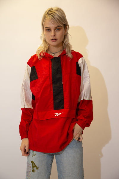 Red in colour, this pullover has a kangaroo-pouch style pocket, Reebok branding on the pocket and back, a hood and draw strings around the neckline and waistline. Finished off with white and black rectangular patches on the shoulders and zipline.