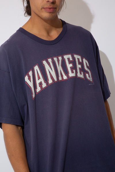 faded navy tee with large yankees spell-out across front and logo graphic on left sleeve