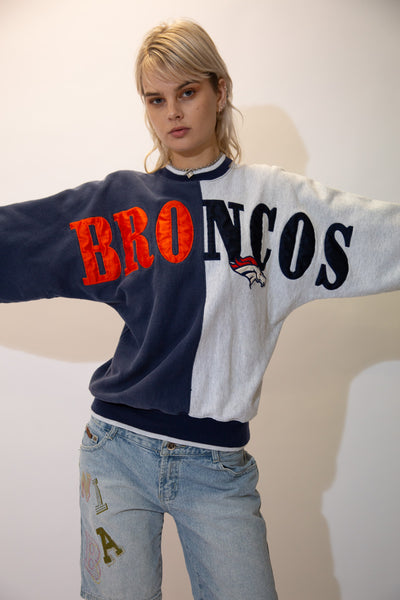 With its rad split navy and grey colour way, striped neckline, cuffs and waistline and large Broncos spell-out in orange and navy blue
