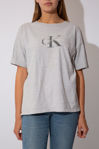 Model is wearing a grey tee that features the CK logo on the font, the tee is oversized on the model