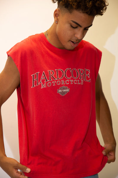 Red in colour, this singlet style tee has a large 'Hardcore' spellout across front with Harley Davidson branding below and dated 2007. On the back, a Harley logo repping State college, Pennsylvania.