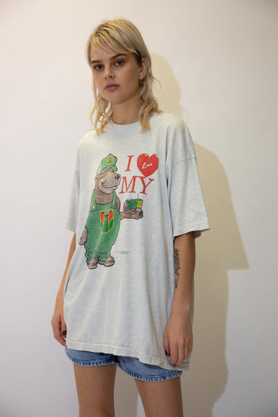 This grey single-stitch tee has a large dungaree-wearing bear on the front holding a tractor.