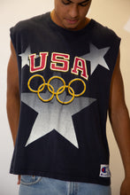 Load image into Gallery viewer, Navy blue in colour, this singlet has a large colour print repping USA in red and the olympic logo in gold. Finished off with a Champion plaque on the left/bottom.