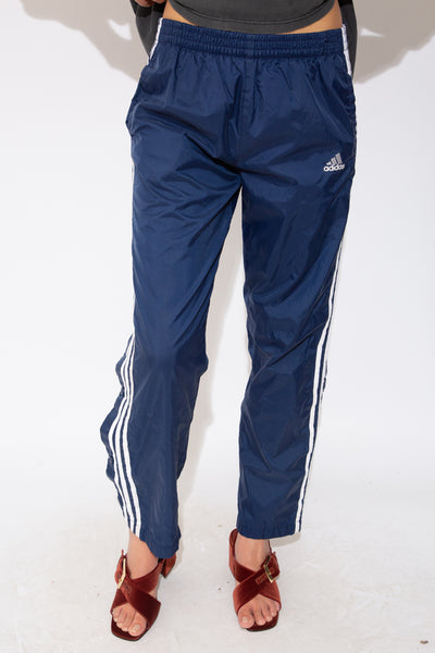 These must-have track-pants are navy blue with the white Adidas logo on the left. Finished off with the classic three white vertical lines and blue metal detachable domes down the sides.