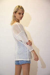 This white crochet tee has midi length arms, a long bodice and a straight cut style.