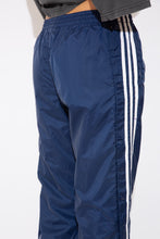 Load image into Gallery viewer, These must-have track-pants are navy blue with the white Adidas logo on the left. Finished off with the classic three white vertical lines and blue metal detachable domes down the sides.