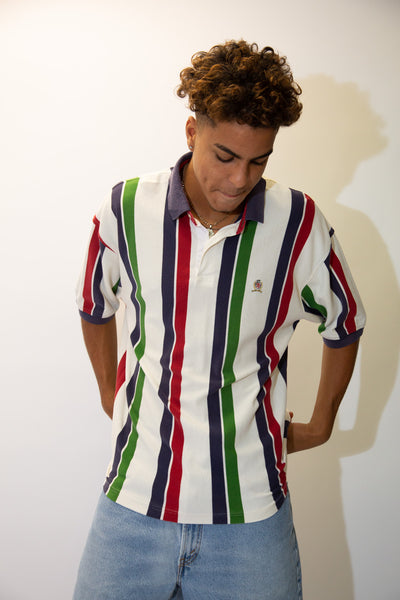 the model wears a white polo with vertical coloured stripes