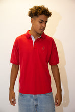 Load image into Gallery viewer, Red in colour in a ribbed material, this short sleeved polo has a blue and white striped inner collar and the Tommy lion branding embroidered on the left chest.