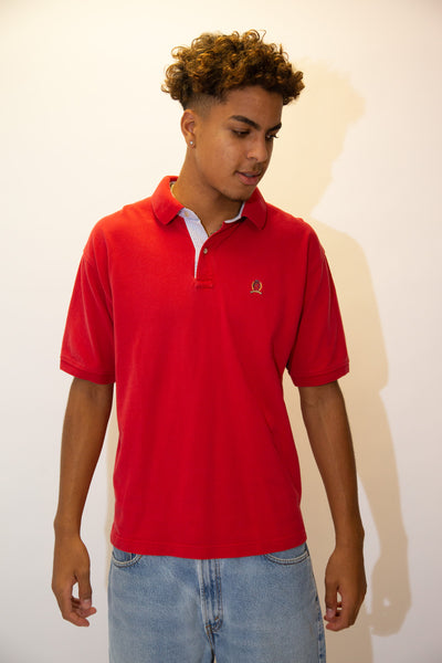 Red in colour in a ribbed material, this short sleeved polo has a blue and white striped inner collar and the Tommy lion branding embroidered on the left chest.