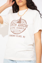 Load image into Gallery viewer, This creamy off-white tee has a brown print of North Arrow Log Homes on the front, single stitching, all while representing Drummond Island, Michigan. Ribbed neckline adds to the fitted style of the tee.