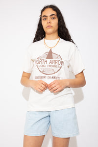 This creamy off-white tee has a brown print of North Arrow Log Homes on the front, single stitching, all while representing Drummond Island, Michigan. Ribbed neckline adds to the fitted style of the tee.