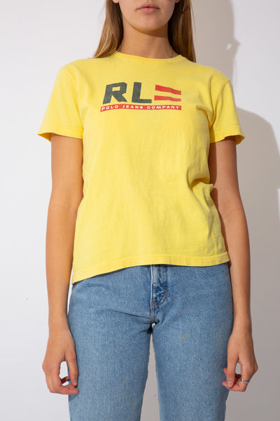 Model is wearing a bright yellow tee featuring RL on the front which is in the shape of the United States flag