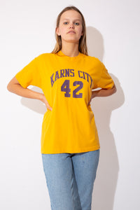"yellow tee with ""Karns City 42"" on the front and number 42 on the back as well (in purple)"
