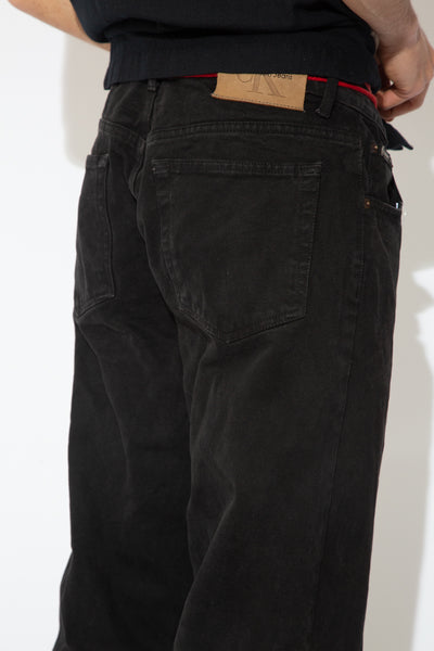 These jeans are black in a straight leg, baggy fit. With a brown leather 'Calvin Klein jeans' plaque at the back and branding on the pocket and button.