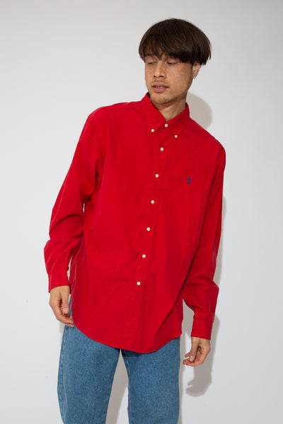 This Ralph Lauren classic fit button-up is red, with a navy blue Ralph Lauren logo on the left chest and white buttons down the front, on the sleeves and on the collar.