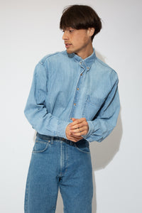 This denim button-up is light-wash blue with brown shell-like buttons down the front and on the sleeves. Finished off with a left breast pocket.