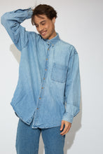 Load image into Gallery viewer, This denim button-up is light-wash blue with brown shell-like buttons down the front and on the sleeves. Finished off with a left breast pocket.