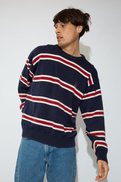 This sweater is navy blue with red and white horizontal stripes. Oversized fit is emphasised by ribbed sleeves, neckline and waistline. Finished off with a lion emblem on the left chest.