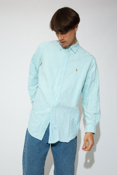 This light blue Ralph Lauren button-up has white buttons down the front and on the sleeves and a colour Ralph Lauren logo on the left chest.