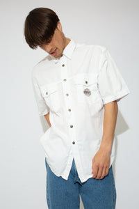 This thick white tee has metal branded closing domes down the front, a collared neckline and two breast pockets with branding on the left one.