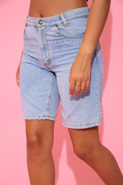 the  model wears a pair of light washed shorts with a mid thigh length