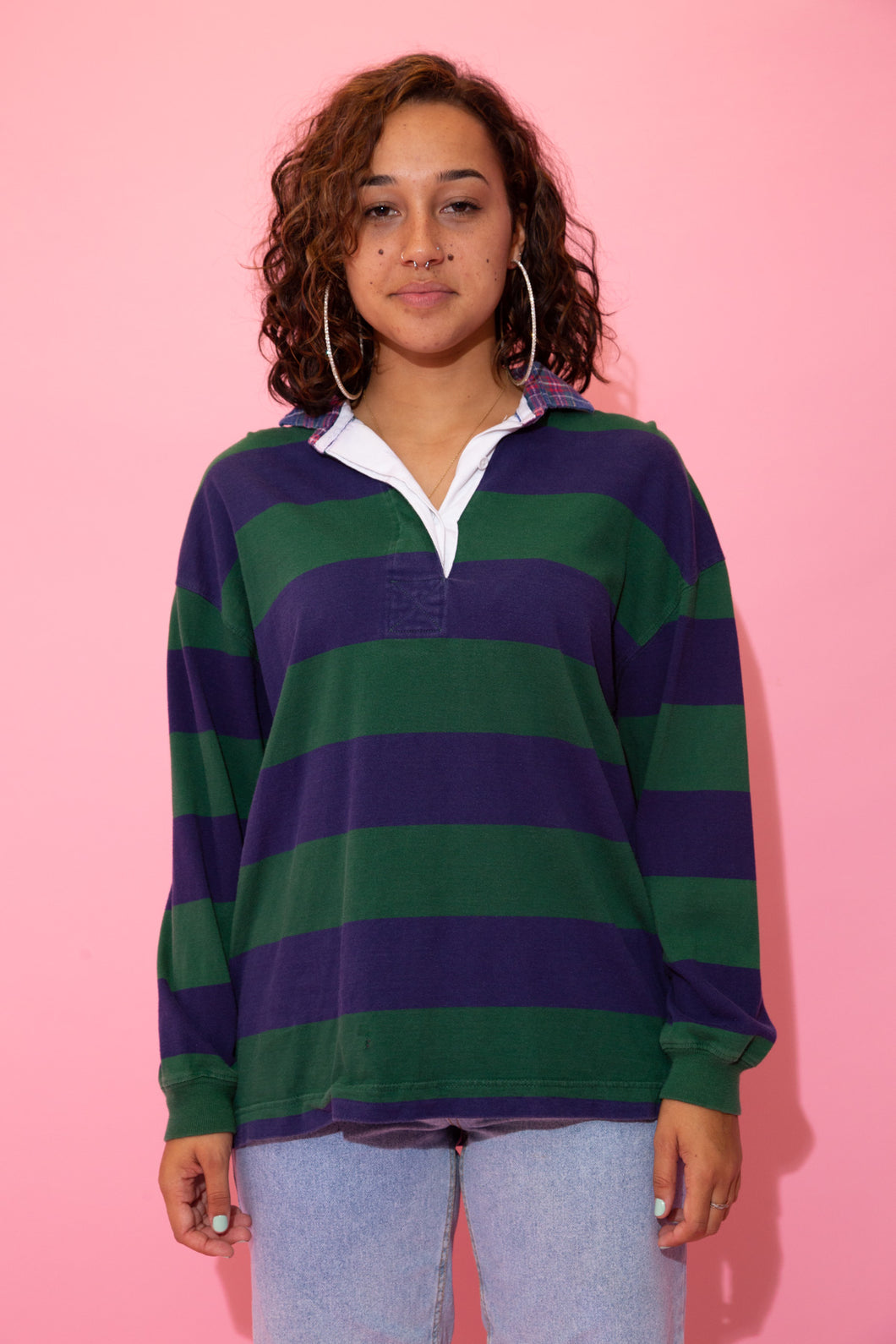 the model wears a navy and green striped rugby