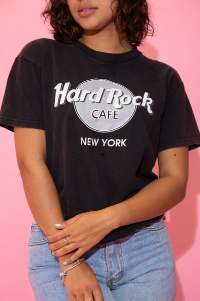 the model wears a faded black tee with a hard rock graphic on the front