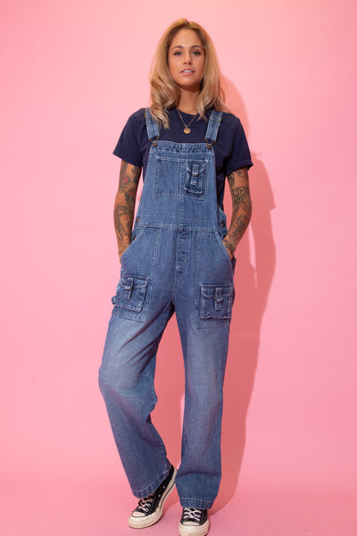 Dark wash blue, these dungarees have white stitching, pockets on the front chest, sides, front legs and back, looped closures, a straight leg fit and Disney branding on the buttons.
