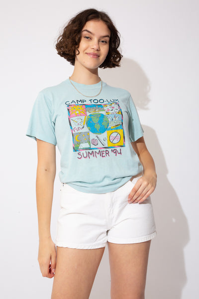 Light blue single-stitch tee with 'Camp Too-Lux Summer '94' and a colourful print of a sun, a bus, earth, painting, stars, no drugs sign and horses on the front.