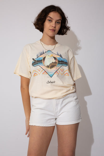 Off-white tee with an eagle print and abstract patterns behind it. 'Colorado' printed below and dated '91.