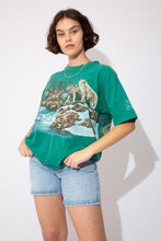 Load image into Gallery viewer, This wolf pack single-stitch tee is green in colour with a large print of a wolf pack in a forest by a stream on the front and back. Stretched out ribbed neckline adds to baggy fit.
