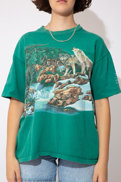 This wolf pack single-stitch tee is green in colour with a large print of a wolf pack in a forest by a stream on the front and back. Stretched out ribbed neckline adds to baggy fit.