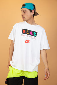 White shortsleeved tee with red Nike branding in the centre of the tee and P.L.A.Y. in bright colours across the front standing for 'participate in the lives of Americas youth'.