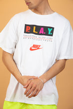Load image into Gallery viewer, White shortsleeved tee with red Nike branding in the centre of the tee and P.L.A.Y. in bright colours across the front standing for 'participate in the lives of Americas youth'.