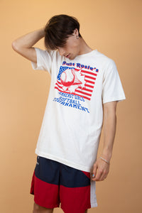 White, single-stitch tee with 'Aunt Rosie's Amherst Girls Softball Tournament' printed in blue, an American flag and a baseball flying in front of it.