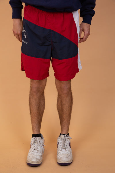 These Nautica shorts are red, blue and white in an abstract shaped pattern. With an appliqué of 'Nautica' and 'North Coast' on the right leg - dated 1983.